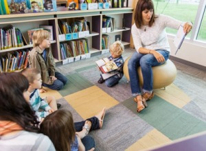 Teacher Reading Book To Children In Library